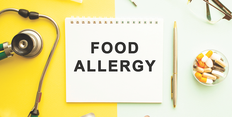 Text FOOD ALLERGY on notebook with stethoscope and pen on yellow background.
